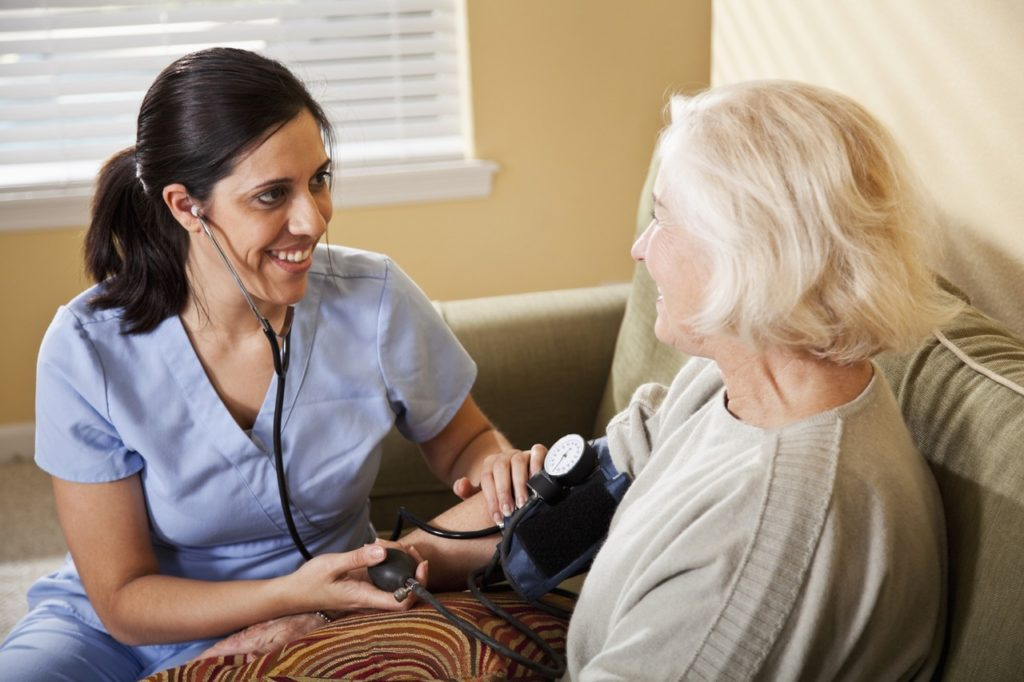 Home healthcare - Hispanic nurse (30s) taking blood pressure of senior woman (60s).